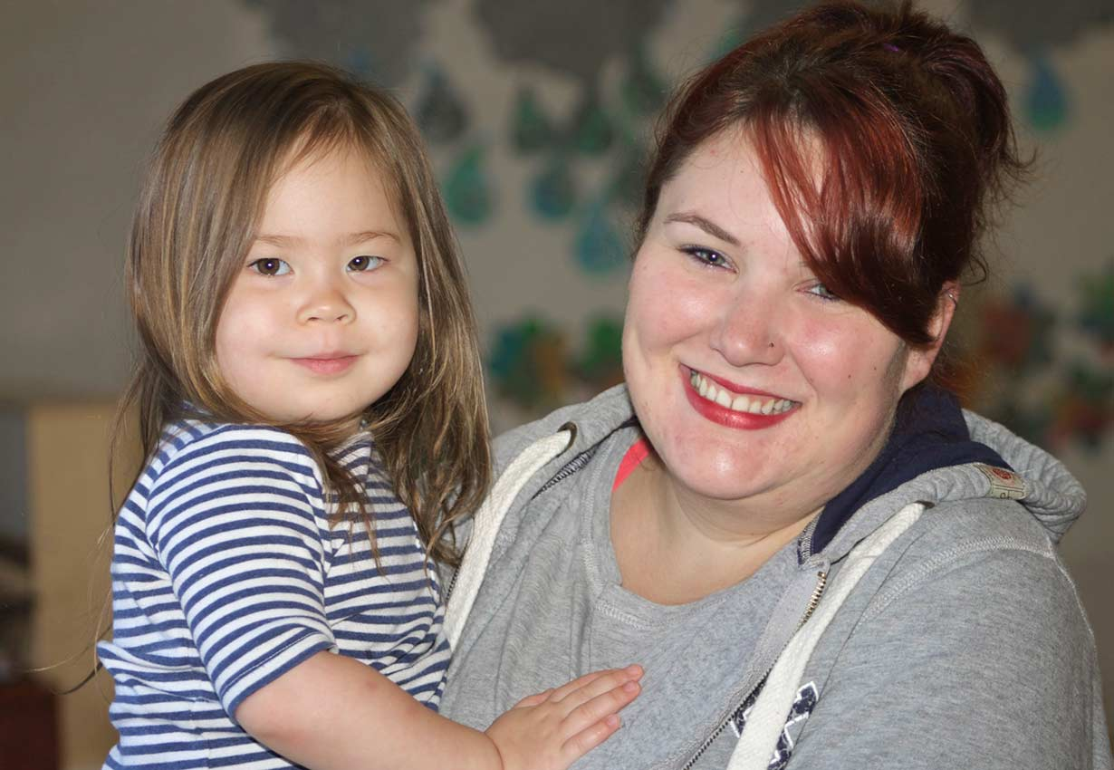 Happy early childhood educator holding a smiling child