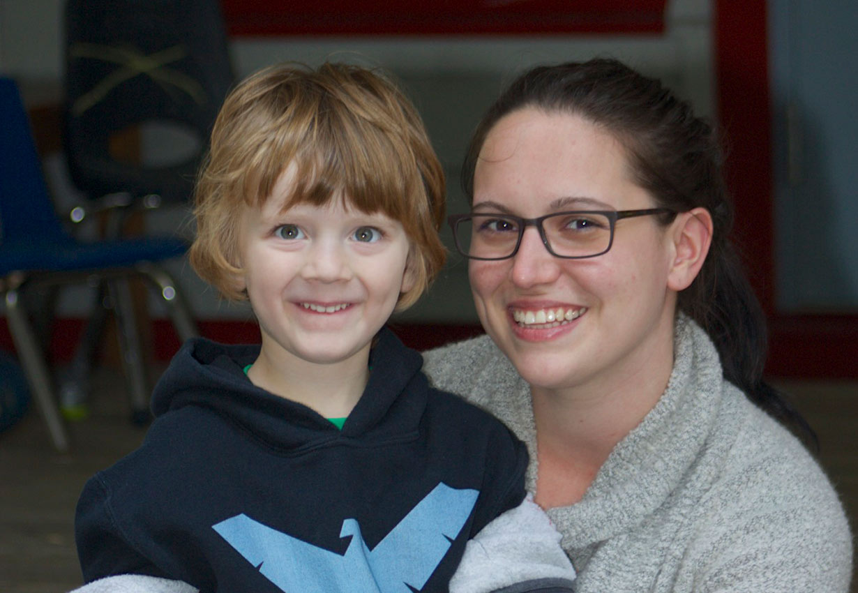 early childhood professional and child smiling at the camera