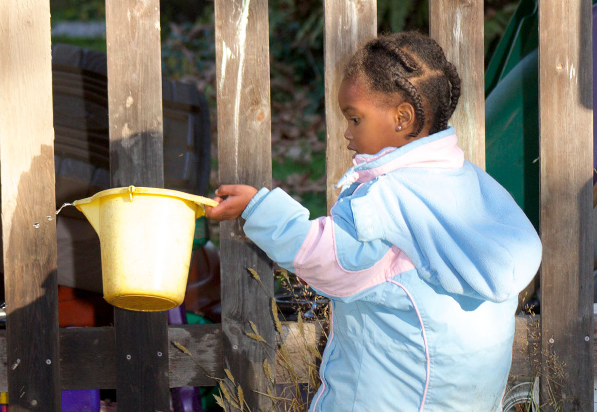 child playing with a bucket of water outside
