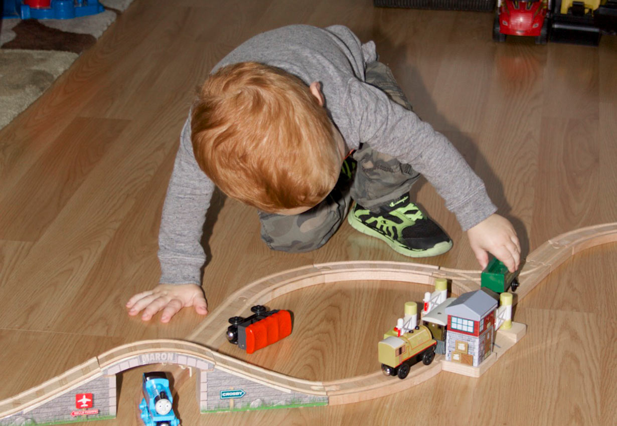 young child playing with a train set