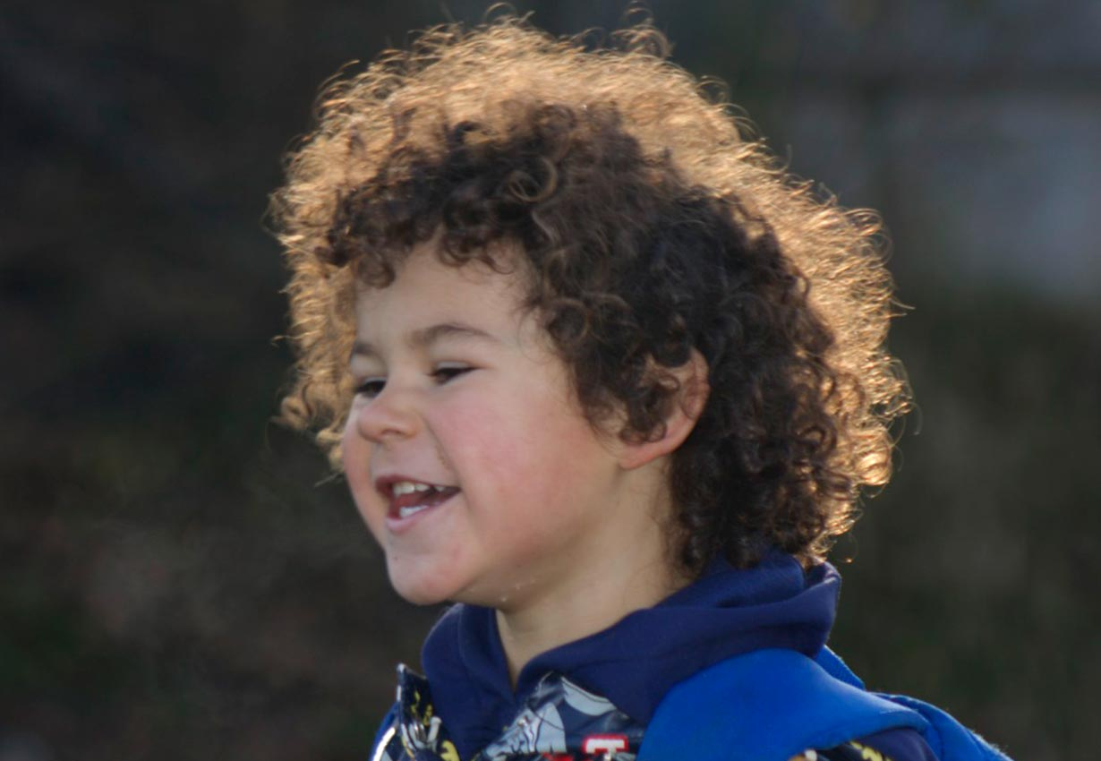 happy child with curly hair outdoors