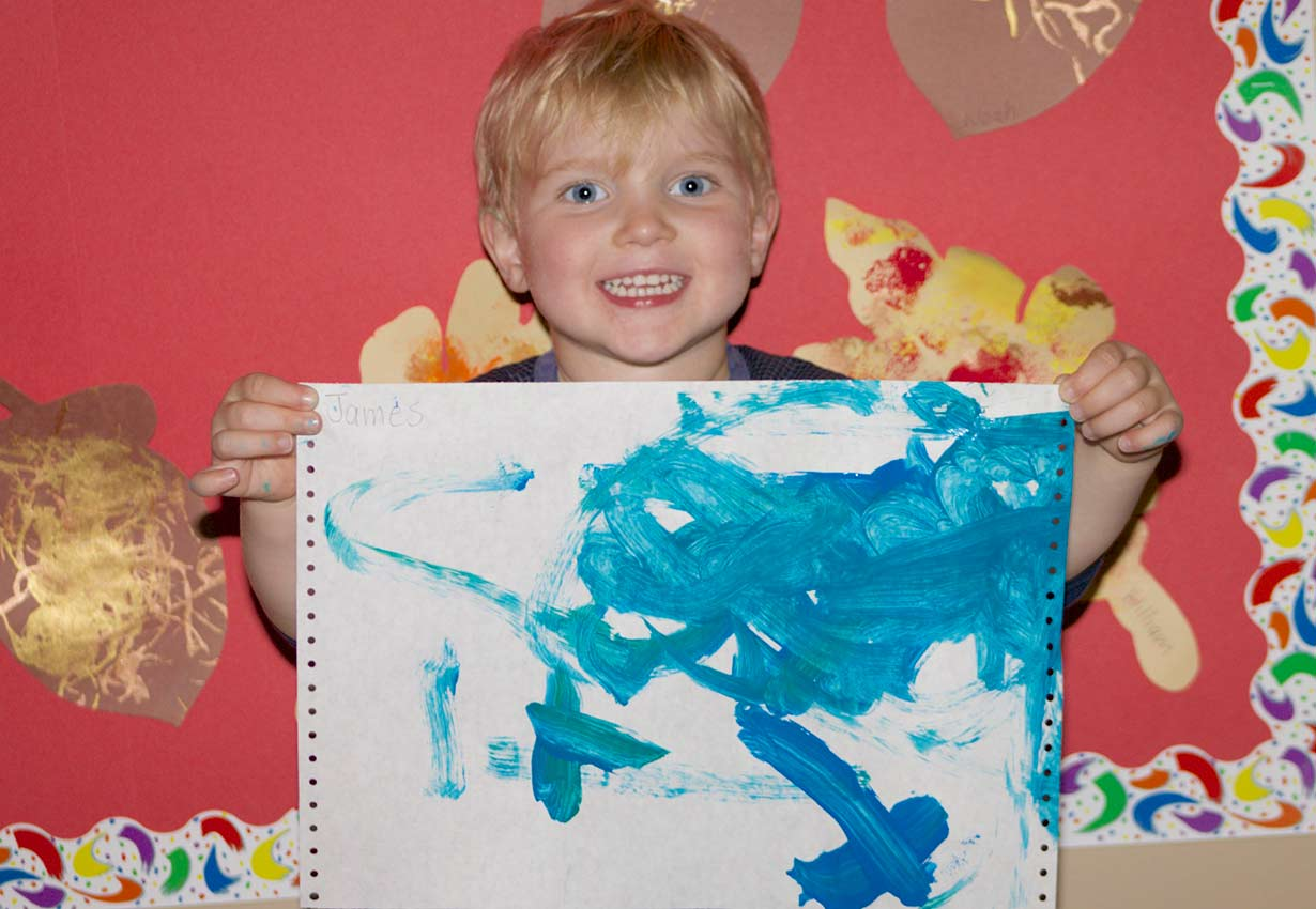 smiling child proudly holding up their painting