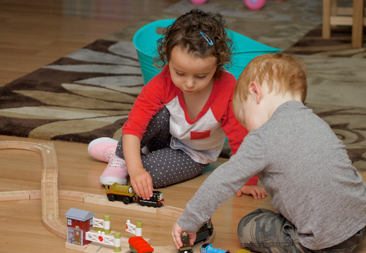 two children playing with trains in child care