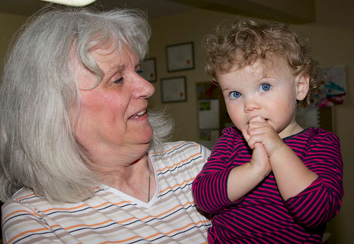 young child being held by early years professional