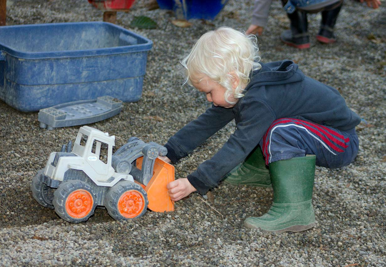 young child scooping gravel with a loader