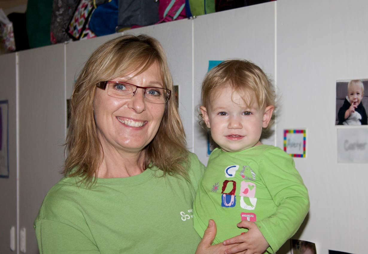 Early childhood educator holding a young child - both wearing green shirts