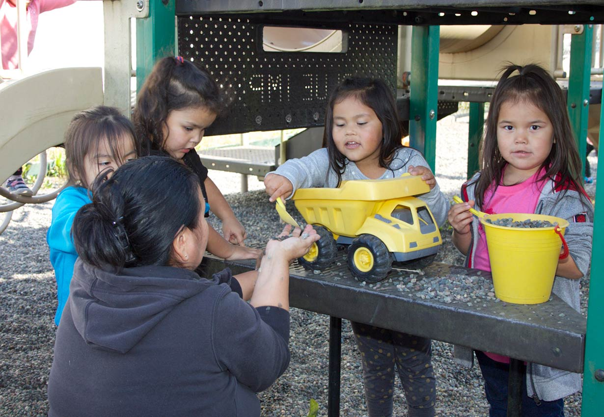 young children playing outdoors with trucks with an early childhood educator