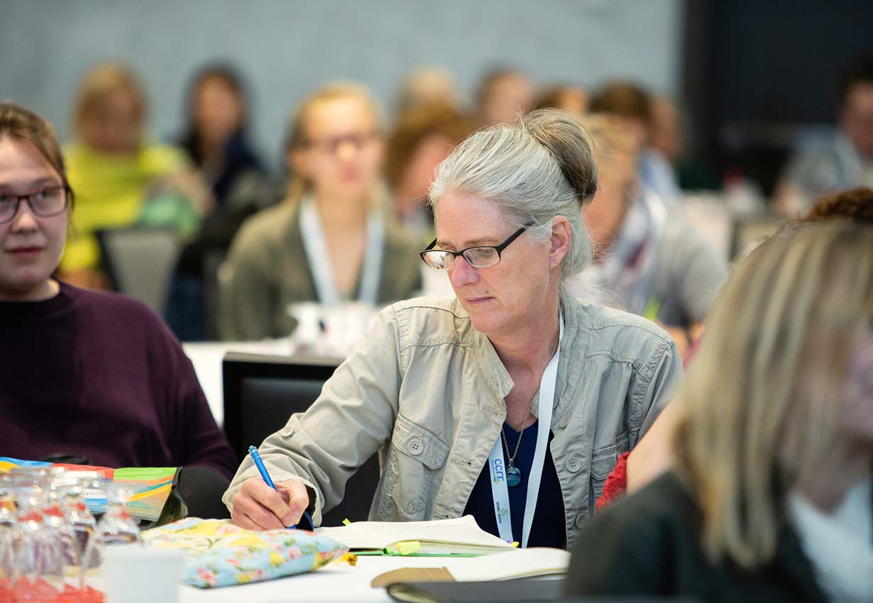 Early childhood educator taking notes at a conference