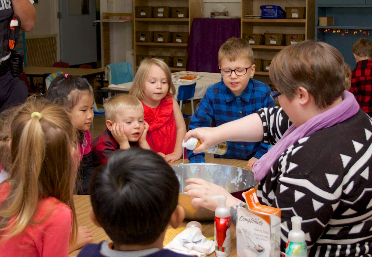 engaged children around a table as an ECE mixes items in a bowl